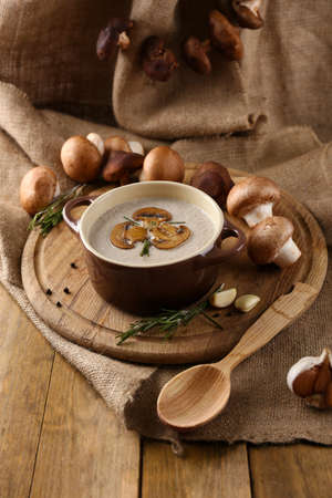 Composition with mushroom soup in pot, fresh and dried mushrooms, on wooden table, on sackcloth  photo