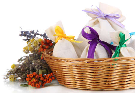 Textile sachet pouches with dried flowers, herbs  and berries  in wicker basket, isolated on white photo