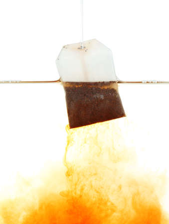 Tea bag dipped in hot water Stock Photo