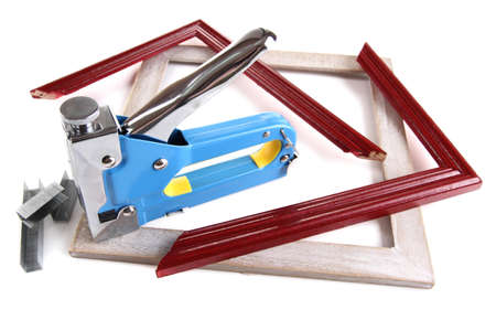 Construction stapler and wooden frames isolated on white photo