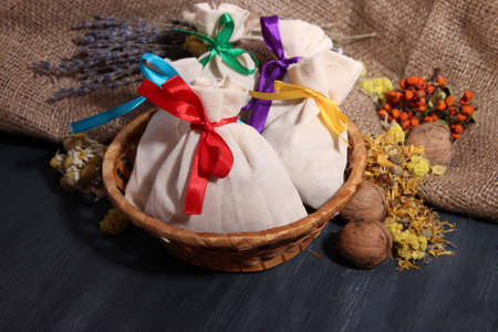 Textile sachet pouches with dried flowers, herbs and berries on wooden table, on sackcloth  photo