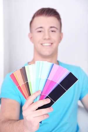 Handsome young man holding palette close up photo