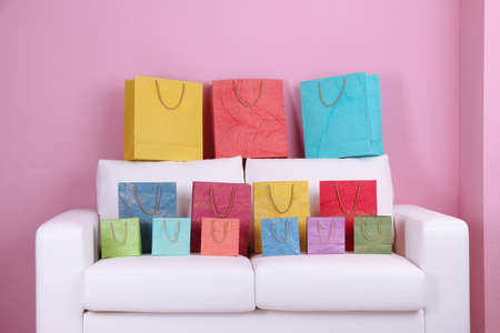 Colorful Shopping Bags On Sofa, On Color Wall Background Stock Photo ...