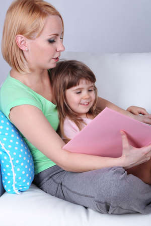 Pretty little girl reading book with mother on sofa on gray background photo