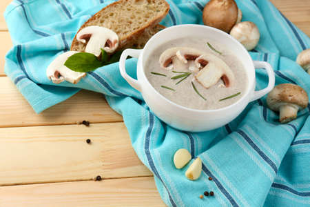 Mushroom soup in pot, on napkin,  on wooden background Stock Photo - 26285342