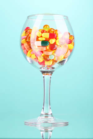 Goblet with pills on green background photo