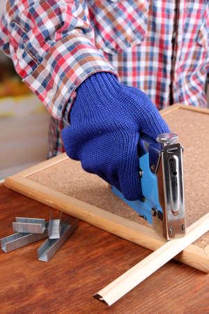 staple gun: Fastening wooden lath and cork board using construction stapler on bright background