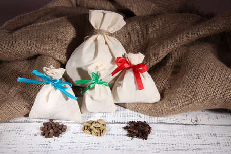 Sacks full with spices, on wooden table, on sackcloth background photo