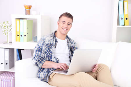 Handsome young man sitting on couch with laptop in room photo