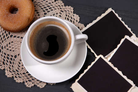 Coffee cup, donut and old blank photos, on wooden background photo