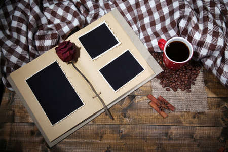 Composition with coffee cup, plaid, and photo album, on wooden background photo
