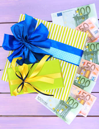 Gift box with money  on color wooden background photo