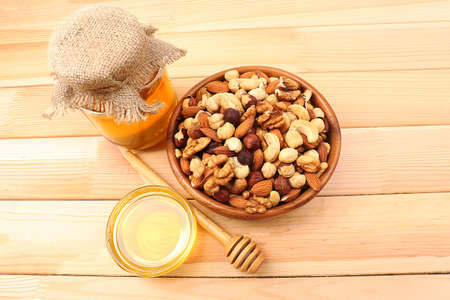 Sweet honey and different nuts on wooden table photo