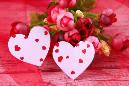 Paper hearts with flowers on table close up photo