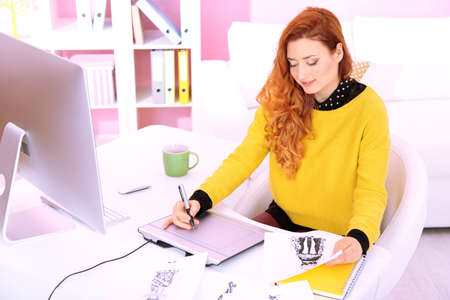 Young woman graphic designer working using pen tablet in workplace Stock Photo