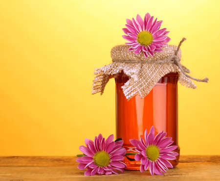 Sweet honey in jar on wooden table on yellow background photo
