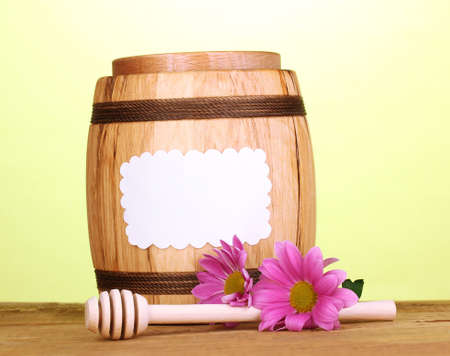 Sweet honey in barrel with drizzler on wooden table on green background photo