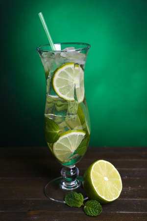 Glass of cocktail with lime and mint on table on dark green background