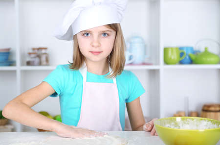 Little girl preparing cake dough in kitchen at home photo