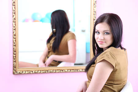 primp: Young beautiful woman sitting front of mirror in room