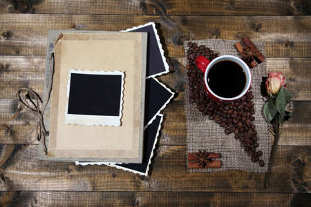 Composition with coffee cup and photo album, on wooden background photo
