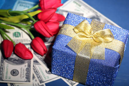 Gift box with money and flowers on color wooden background photo