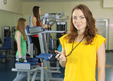 Young trainer and womans engaged in simulator in gym photo