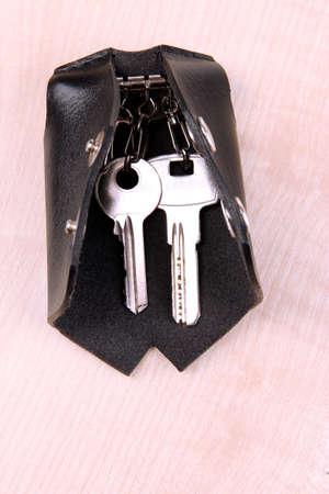 doorkey: Caso chiave di cuoio nero su sfondo di legno Archivio Fotografico