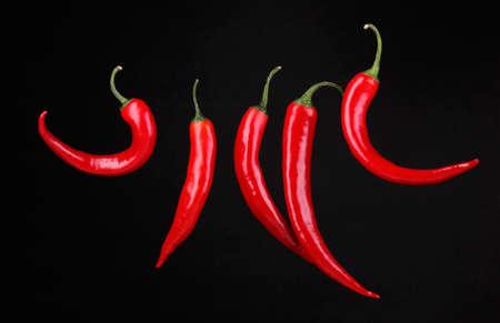 pepe nero: Red hot chili peppers isolato su nero Archivio Fotografico