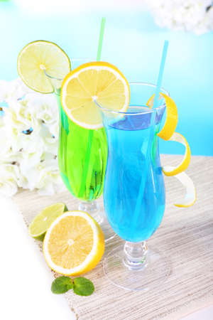 Glasses of cocktails on table on light blue background photo