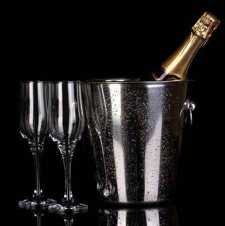 Bottle of champagne in bucket and goblets isolated on black photo