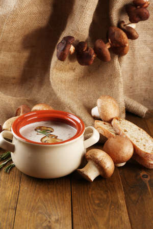 Composition with mushroom soup in pot, fresh and dried mushrooms, on wooden table, on sackcloth background photo
