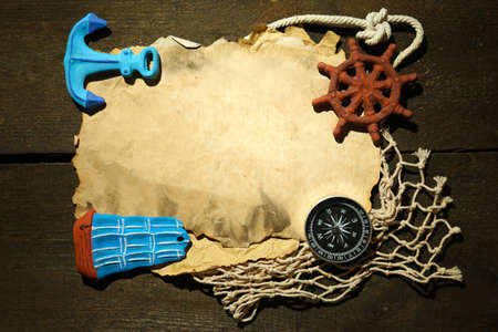 Old paper with sea accessories, isolated on wooden background photo