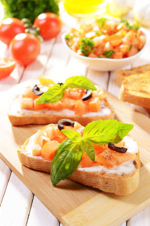 Delicious bruschetta with tomatoes on cutting board close-up photo