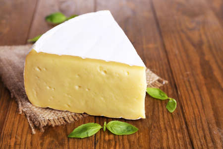 chees: Tasty Camembert cheese with basil, on wooden table Stock Photo