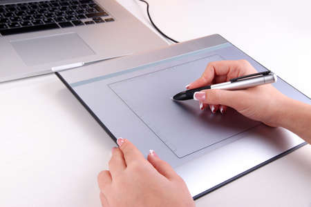 Female hand using graphics tablet on table close up photo