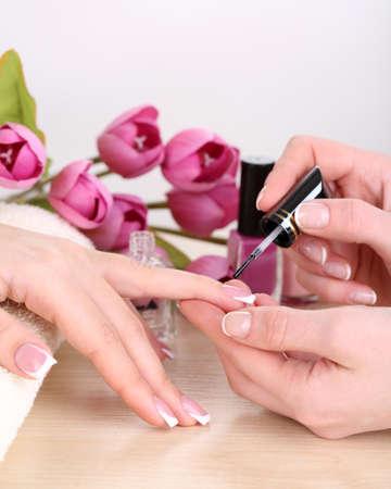 Manicure process in beauty salon close up photo