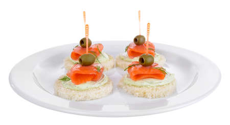 Delicious canapes on plate isolated on white photo