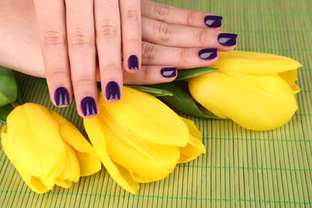 Beautiful woman hands with flowers on bamboo background photo