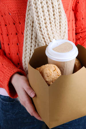Woman holds box with coffee and cookies close-up photo