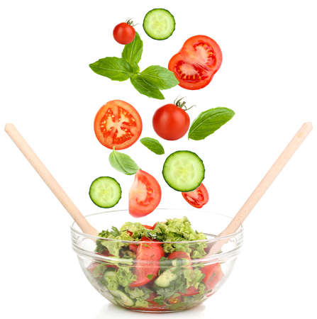 Fresh mixed vegetables falling into bowl of salad isolated on white photo