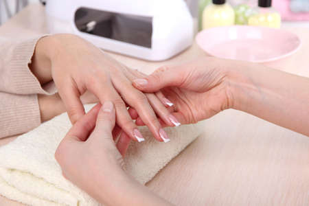 Manicure process in beauty salon close up photo