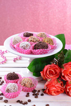 Set of chocolate candies on table on pink background photo