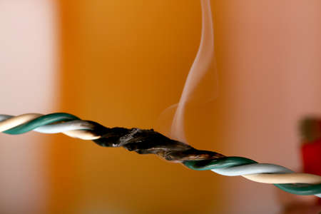 Short circuit, burnt cable, on dark color background photo