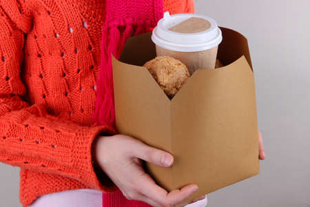 Woman holds box with coffee and cookies on grey background photo