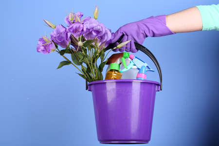 Housewife holding bucket with cleaning equipment on bright background. Conceptual photo of spring cleaning.  photo