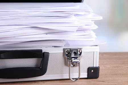 Briefcase full of papers, on wooden table, on light background photo