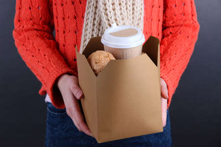 coffee breaks: Woman holds box with coffee and cookies on black background Stock Photo
