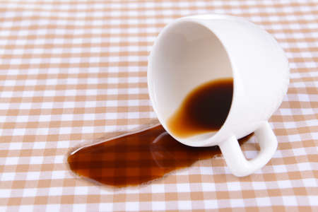 coffee spill: Overturned cup of coffee on table close-up Stock Photo
