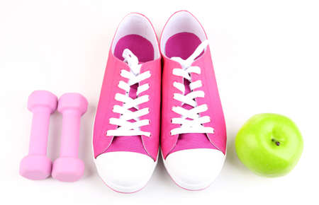 Sneakers and sport equipment. Conceptual photo of fitness progress. Isolated on white photo